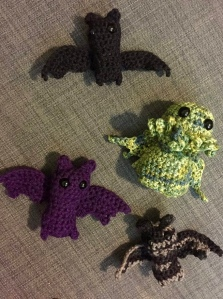three crocheted bats, one purple, one black and one grey and black striped, along with a variegated green and yellow crocheted Cthulhu on a grey background