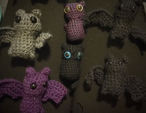 four crochet bats, black grey and purple, along with two crocheted cats that have very large eyes, all on a black background