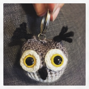 A crocheted owl head, palm sized and very round, with black tufts for ears and large yellow eyes.