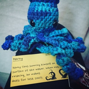 "A variegated blue octopus with black eyes sitting on a small yellow card that contains the following story: ""Davey likes sunning himself on the surface of the water.  When not relaxing, he makes deals for lost souls."""