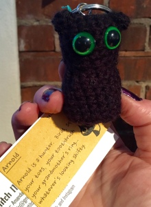 """A small crocheted black cat keychain with big green eyes and a card attached that reads """"Arnold is a hunter.  Birds, squirrels, your toes, your toothbrush, your grandmother's ring....whatever's looking shifty."""""""