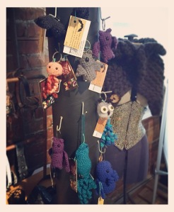 A black column is on a table and contains a number of hooks.  Most hooks are empty but some contain hanging crocheted creatures, ten in all.