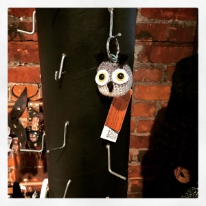 A black display column is covered in a dozen or more empty hooks.  In the middle hangs on crocheted creature keychain, an owl called Herbert.