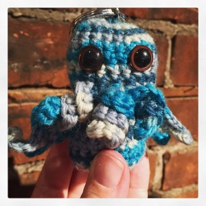 A blue and grey striped crocheted Cthulhu with a keychain ring attached to the top of his head, being held in front of a brick background